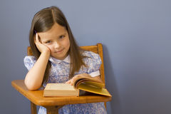 Back to School. Little girl sitting at a wooden school desk Royalty Free Stock Image