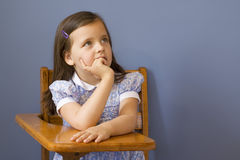 Back to School. Little girl sitting at a wooden school desk Stock Image