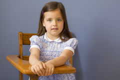 Back to School. Little girl sitting at a wooden school desk Stock Images