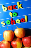 Back to school. Message with colorful letters on blue board and red apples Stock Photos