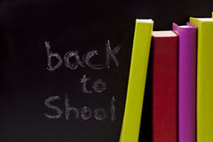 Back to School. Letters written on a blackboard with colorful books (selective focus Royalty Free Stock Images