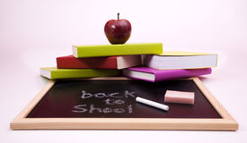 Back to School. Letters written on a blackboard with colorful books (selective focus Stock Photos