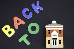 Back to School. Blackboard spelling Back to School with miniature of a schoolhouse Stock Photography