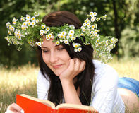Back to school. Happy smiling girl in garland reading book outside Stock Photo