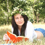 Back to school. Happy girl in garland reading book outside Royalty Free Stock Photo