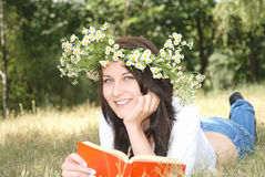 Back to school. Happy girl in garland reading book outside Stock Photography