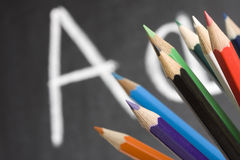Back to school. Crayons in front of a blackboard Stock Image