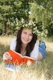 Back to school. Happy smiling girl in garland reading book outside Royalty Free Stock Images