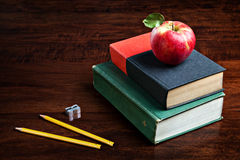 Back to School. A wooden tabletop with a stack of books, a pretty red apple, two pencils and a small sharpener Stock Photography