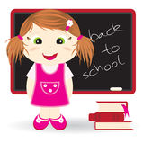 Back to school. Cute girl standing in front of the blackboard Stock Image
