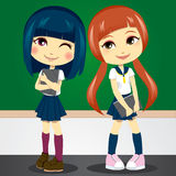Back to School. Two shy teenage girls in student uniform carrying folders on first day of school Stock Photos