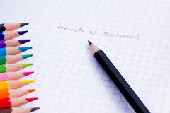 Back to school. A shot of some colourful pencils on a book Stock Image