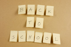 Back to school. Writing back to school is spelled in a sheet of paper affixed to the wall brown carton Stock Images
