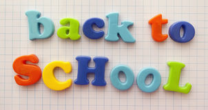 Back to school. Message ' back to SCHooL' in a mixture of colorful upper and lower case letters on a background covered by small squares Royalty Free Stock Image