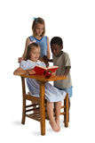 Back to School. Three young children of different races reading together at a wooden school desk. Isolated on a white Royalty Free Stock Image