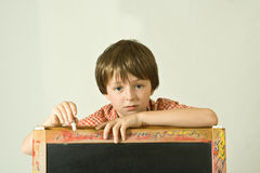Back to School. Young boy posing with a children's blackboard. Horizontal head and shoulders portrait, isolated against a white background royalty free stock images