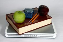 Back to school. Laptop, book, pencil, calculator, and two apples Stock Photography