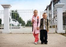 Back to school. Two elementary students in front of the school Stock Images