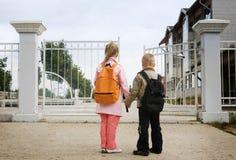Back to school. Two preschoolers entering the school stock images