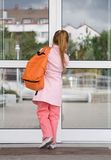Back to school. Little girl entering the school building stock images