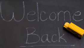 Back To School. A black board with the words welcome back, and also a small toy school bus Royalty Free Stock Images