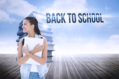 Back to school against stack of books against sky. The word back to school and student holding laptop against stack of books against sky Royalty Free Stock Images