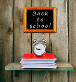 Back to school. An alarm clock and writing-books Royalty Free Stock Photo
