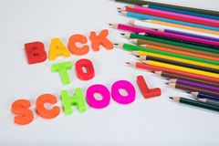 Back to school alphabet letters and colour pencils. Back to school written with colourful alphabet learning letters beside coloured children pencils on a plain Royalty Free Stock Photo