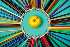 Back to school. Apple and colored pencils are laid out in a circle