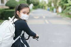 Back to school. asian child girl wearing face mask with backpack biking a bicycle and going to school .Covid-19 coronavirus