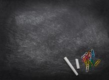 Back to school Background. Black chalkboard with chalk pieces and paper clips. School supplies. Flat lay. Copy space royalty free stock images