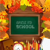 Back to school background with blackboard, alarm clock, pencils, notepad and autumn leaves frame on wooden surface. Royalty Free Stock Photography