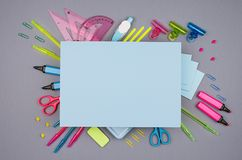 Back to school background - blank blue paper with copy space and colored different stationery on grey table background. royalty free stock images