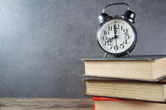 Back to school background with books and alarm clock. Over chalkboard Royalty Free Stock Photo