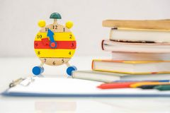 Back to school background with books and alarm clock over chalkboard Royalty Free Stock Photos