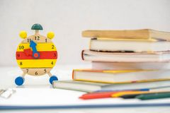 Back to school background with books and alarm clock over chalkboard Royalty Free Stock Images