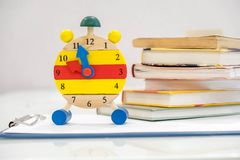Back to school background with books and alarm clock over chalkboard. 12 o`clock. Time management concept. Close-up Of Alarm Clock Royalty Free Stock Photo