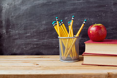 Back to school background with books, pencils and apple over chalkboard. And wooden table Royalty Free Stock Photos