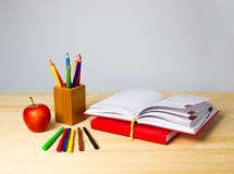 Back to school background with books, pencils and apple over wooden table Stock Photos