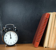 Back to school background with chalkboard, books and alarm clock Royalty Free Stock Photography