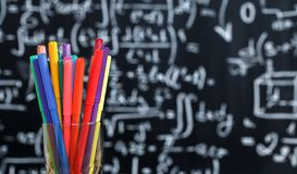Back to school background with colorful felt pens and blurred math formulas written by white chalk on the black school stock photos