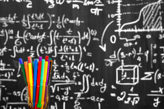 Back to school background with colorful felt pens and blurred math formulas written by white chalk on the black school chalkboard. Stock Photography
