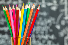 Back to school background with colorful felt pens and blurred math formulas written by white chalk on the black school chalkboard Stock Image