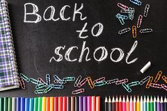 Back to school background with colorful felt tip pens, pencils, clips, notebook and the title Back to school written by Stock Images