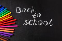 Back to school background with colorful felt tip pens and title Back to school written by white chalk on the school Stock Photo