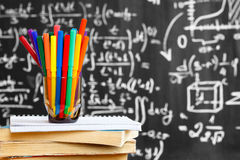 Back to school background with colorful pencils on the books and notebook and the title `Back to school` written by white chalk. On the black school chalkboard Royalty Free Stock Image