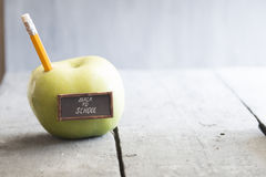 Back to school background. Back to school idea - text, yellow pencil and green apple on the table Royalty Free Stock Images