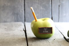 Back to school background - inscription and pencil and apple on the table, toned. Back to school idea - text, yellow pencil and green apple on the table Royalty Free Stock Image