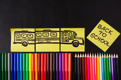 Back to school background with a lot of colorful felt-tip pens and colorful pencils, titles `Back to school`. And drawing of school bus drawn on the yellow Stock Images