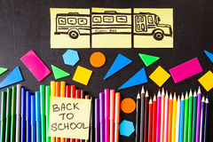 Back to school background with a lot of colorful felt-tip pens and colorful pencils, titles `Back to school`. And drawing of school bus drawn on the yellow Royalty Free Stock Photography